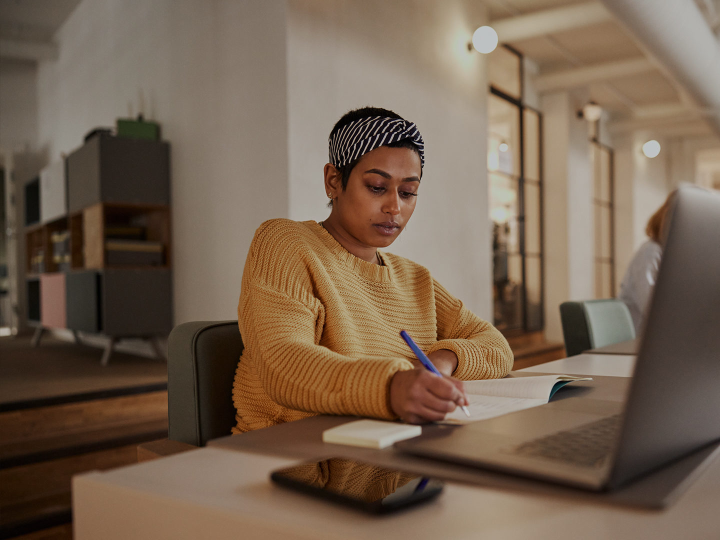 Woman writing in notebook in office space