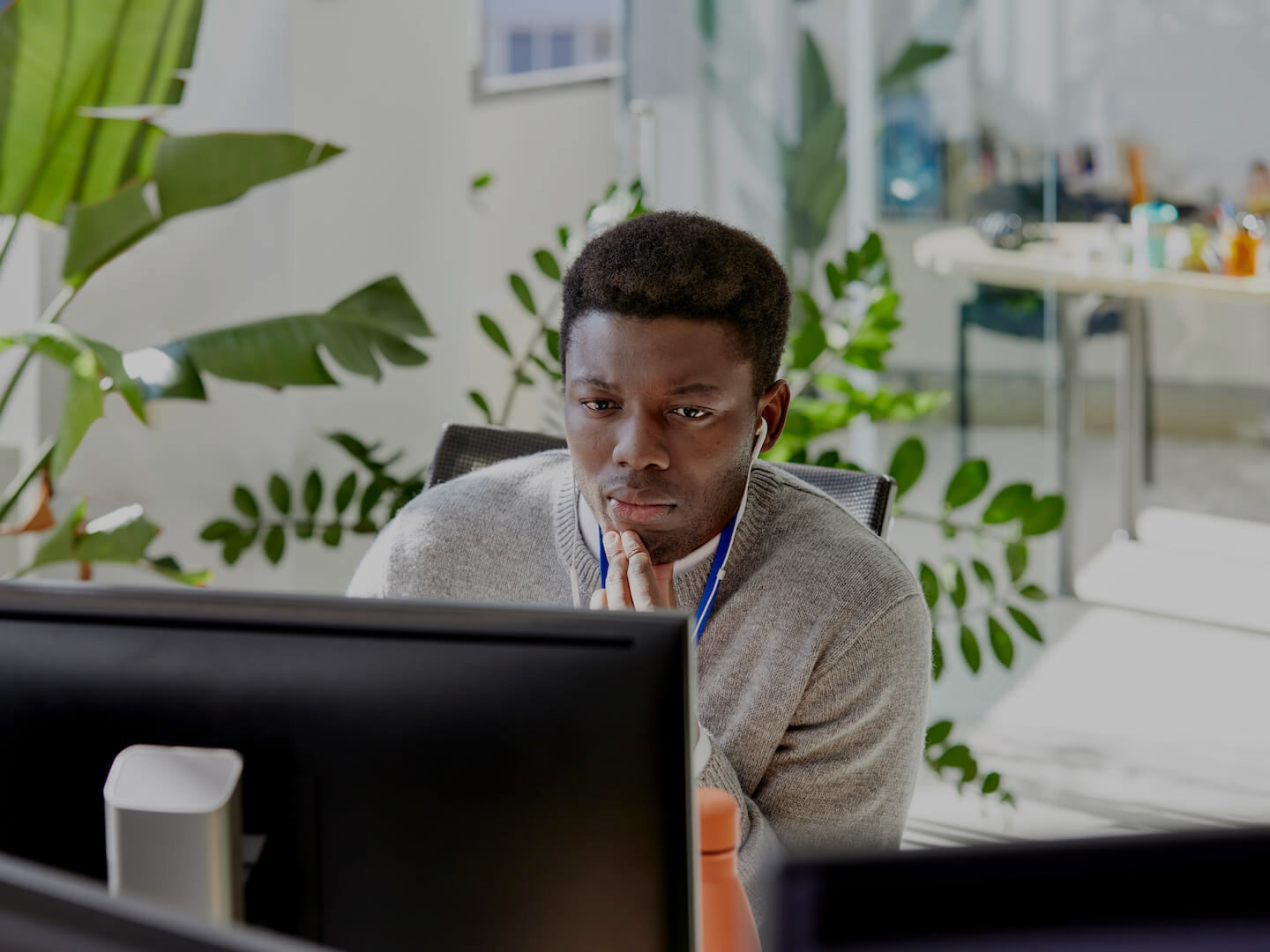 Man working at desktop with plants in the background