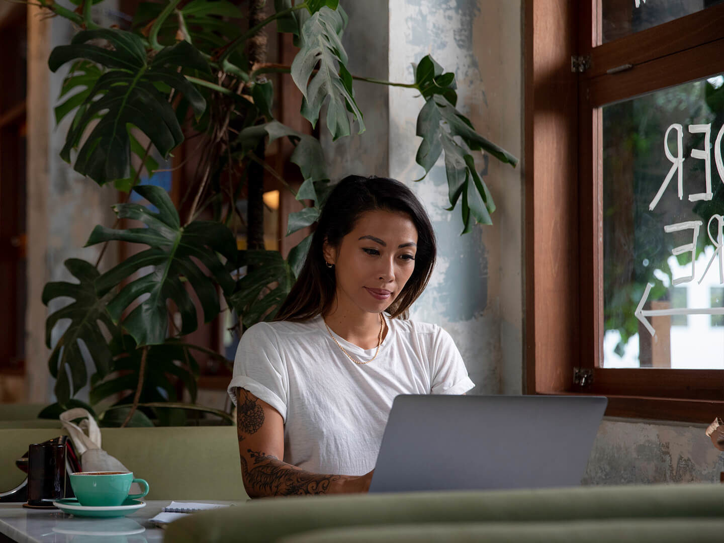 Woman with tattoo working from coffee shop
