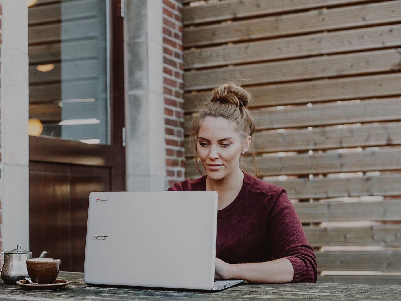 Woman on her laptop outside learning tech skills online