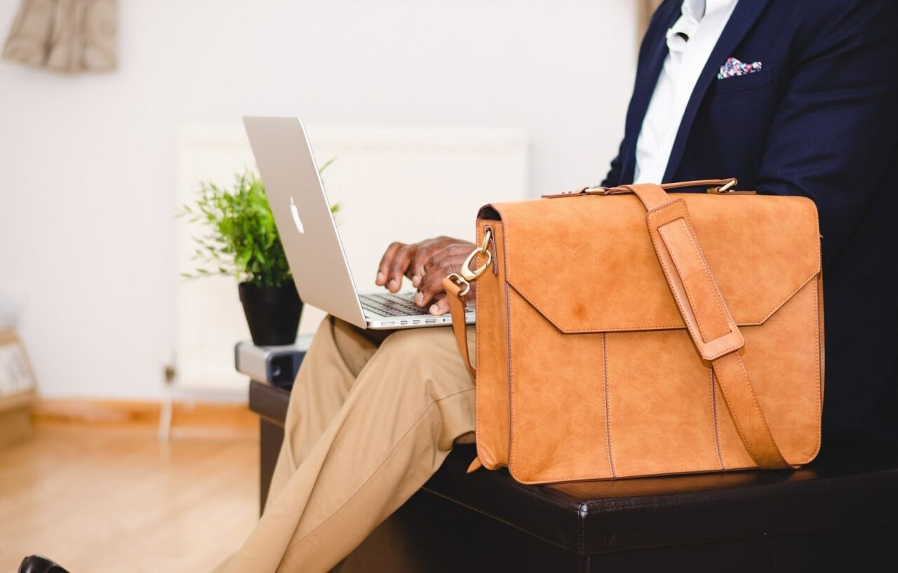 Person with laptop open on lap and briefcase next to them