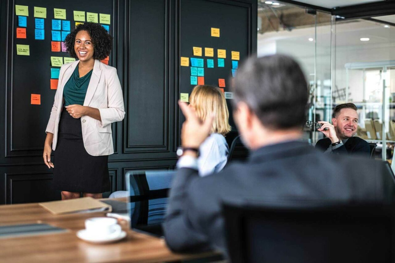 Smiling Woman in Blazer and Skirt Presenting to Colleagues 1