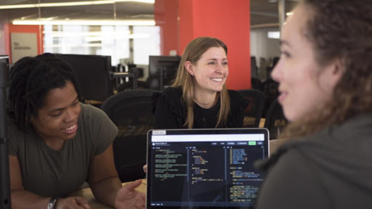 Women technologists around laptop