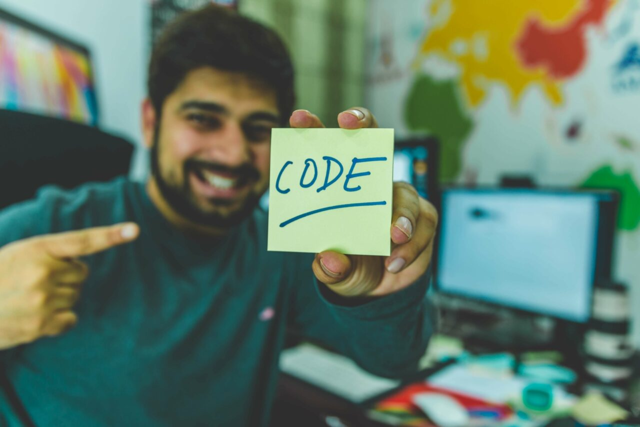 Male programmer with postit note