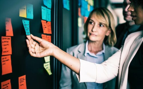 Older woman looks at younger colleague holding post it