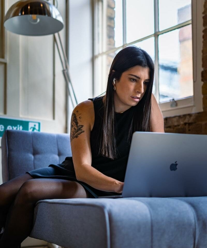 Woman studying from couch on mac